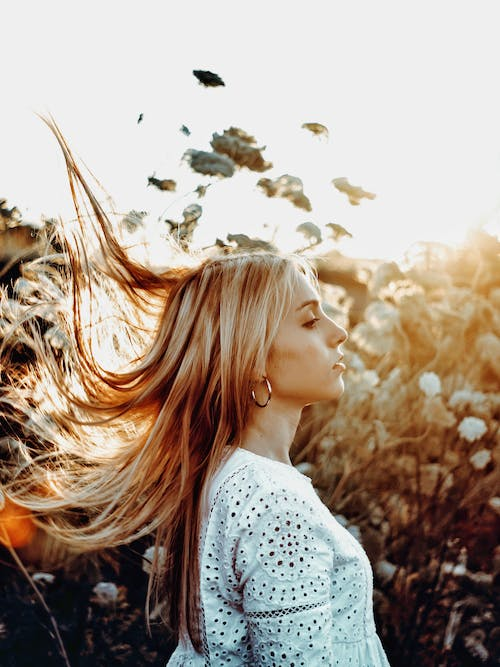 Young woman with flying hair in blooming garden