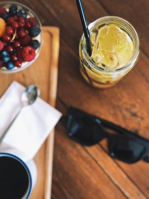 Glass of lemonade near wooden board