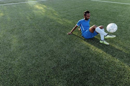 緑の芝生のフィールドに座っている青いtシャツと青いショートパンツの少年