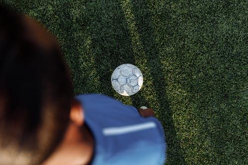 緑の草の上に横たわっている青いシャツの人