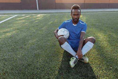 青いクルーネックtシャツと白いショートパンツの男が緑の芝生のフィールドに座っている間
