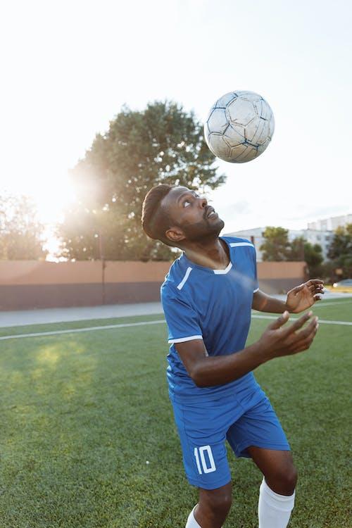 白のサッカーボールを保持している青と白のナイキクルーネックtシャツの男
