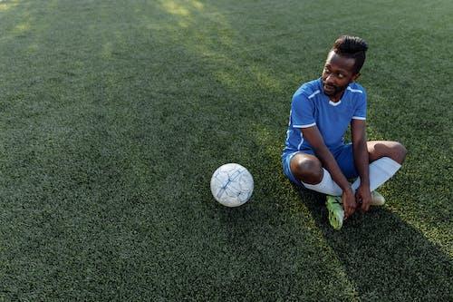 緑の芝生のフィールドでサッカーをしている青いクルーネックtシャツと黒のショートパンツの少年