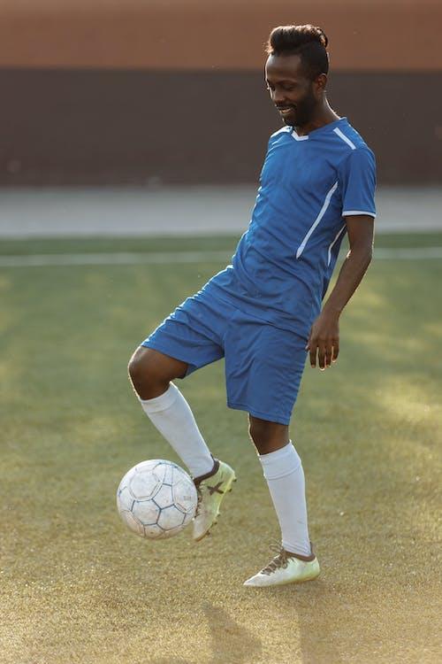 青いサッカージャージーキックサッカーボールの男