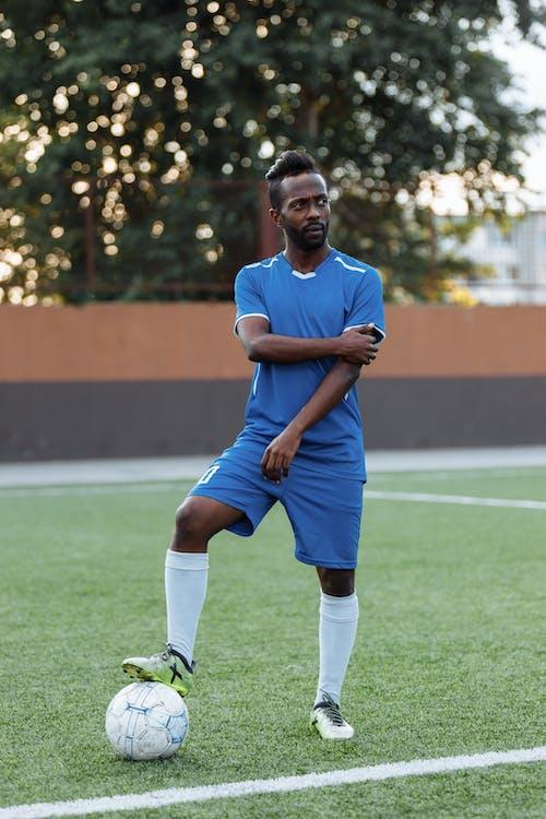 青と白のサッカージャージーシャツとショートパンツの男が緑の芝生のフィールドで実行中