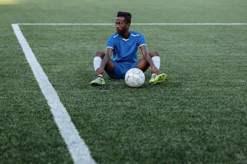 緑の芝生のフィールドに横たわっている青と白のナイキサッカージャージーの男
