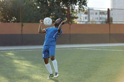 ブルージャージーシャツとショートパンツでサッカーをする男