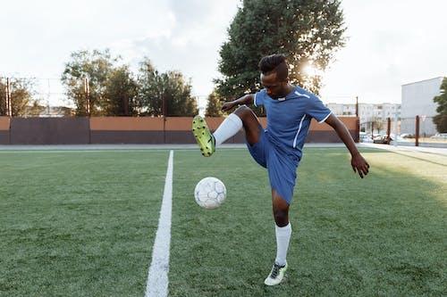 Man In Blauw Shirt Voetballen