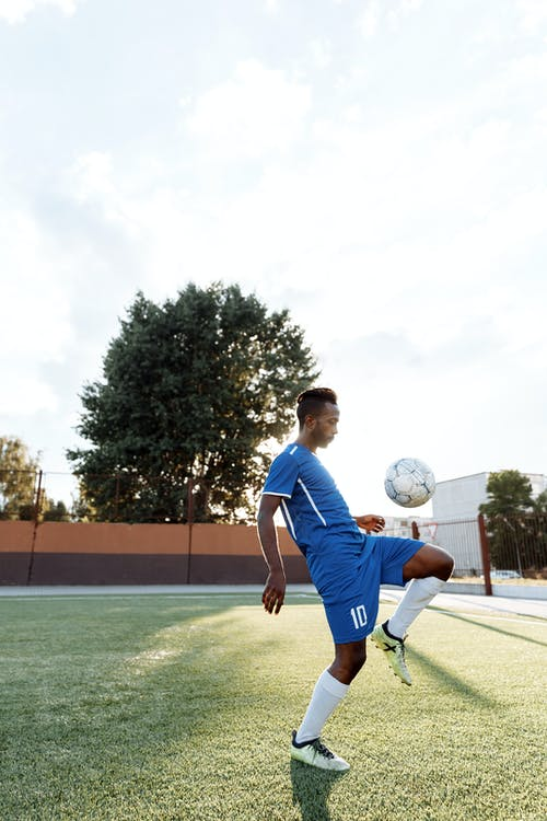 Man in Blue Shirt Playing Soccer