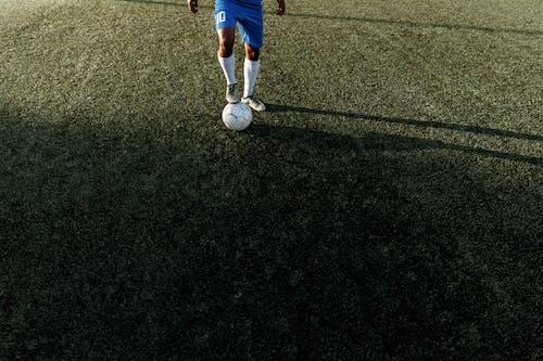緑の芝生のフィールドで青いショートパンツと白いサッカーボールの少年