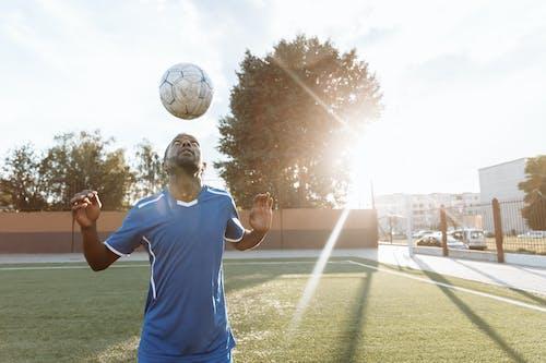 白いサッカーボールを保持している青い乗組員の首のtシャツの男