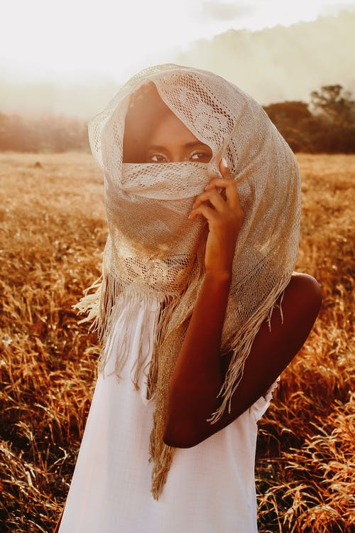 African American female in white dress and headscarf standing in grassy field under sunset sky and looking at camera