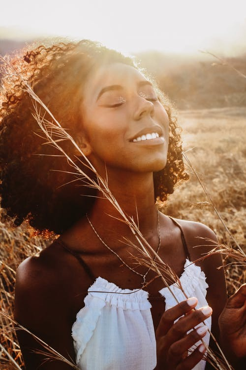 Cheerful black woman in field under evening sky