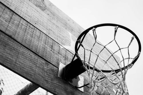 Black and white of basketball hoop hanging on wooden board located on sports ground on street