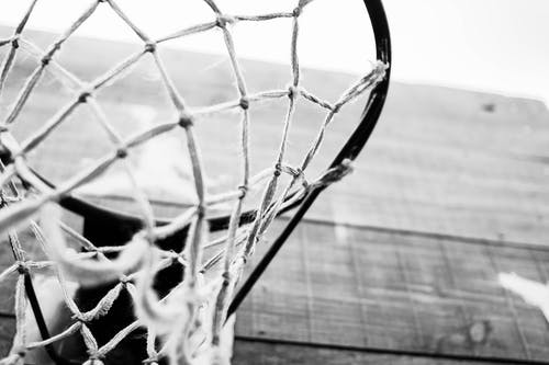 Low angle closeup of black and white basketball hoop hanging in wooden board in sports ground