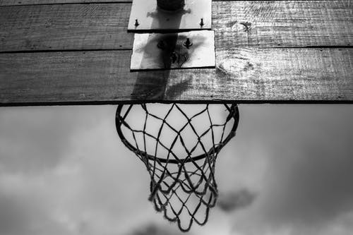 From below of black and white wooden backboard with basketball net hoop hanging against cloudy sky