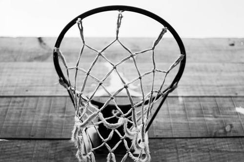 Low angle of black and white basketball mesh net and hoop hanging on wooden backboard on sports ground