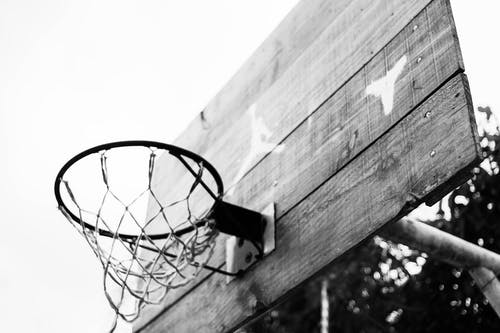 From below of black and white basketball hoop hanging on backboard on sports ground in park