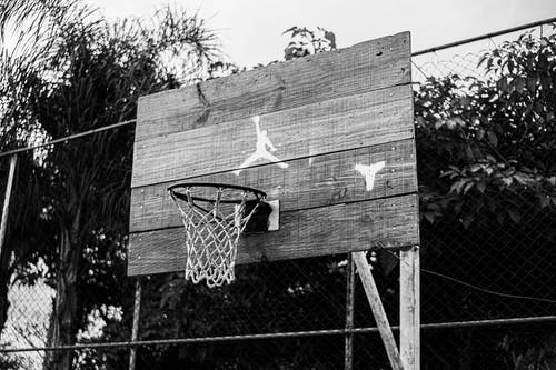 Fenced basketball court with hanging hoop in park
