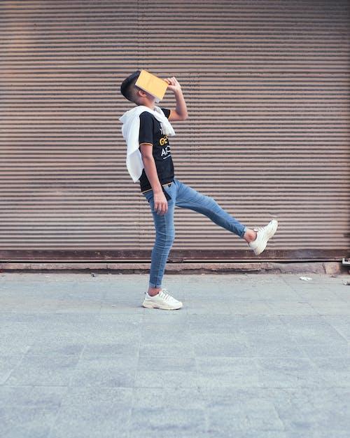 Woman in White Shirt and Blue Denim Jeans Walking on Sidewalk