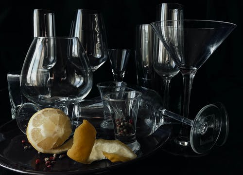 Composition of glasses for different alcohol drinks served on table with fresh lemon and scattered peppercorns against black background