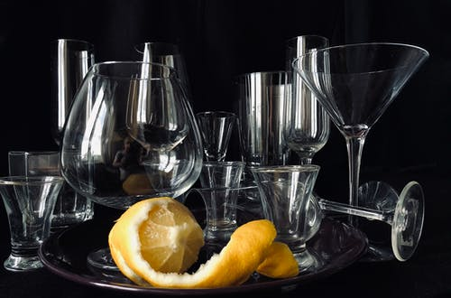 Fresh sour lemon served on tray with collection of glassware