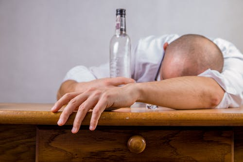 Man in White Dress Shirt Holding Glass Bottle on Brown Wooden Table
