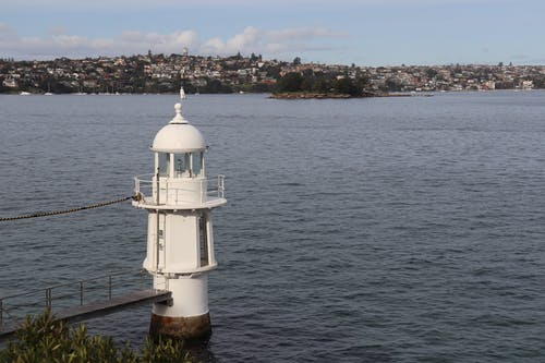 White and Black Lighthouse Near Body of Water