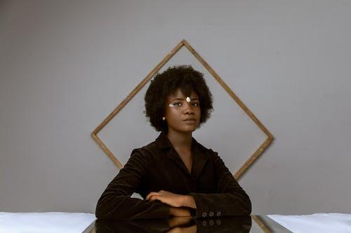 Elegante Jonge Zwarte Vrouw Met Afro Haar Rusten In De Kamer In De Buurt Van Versierde Muur Met Frame