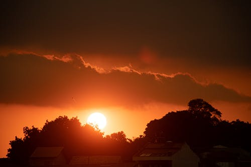 Silhouettes of lush trees and cottages under bright orange sundown in cloudy sky