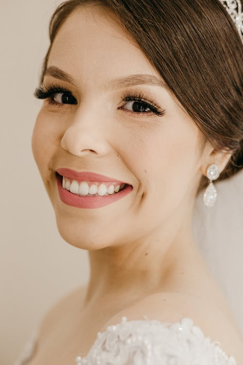 Happy young fiancee with makeup and dark hair tied up looking at camera on beige background
