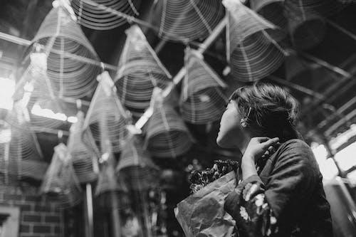 Unrecognizable Asian pilgrim contemplating incense coils in Buddhist church