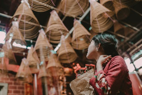 Anonymous ethnic tourist admiring incense coils in oriental temple