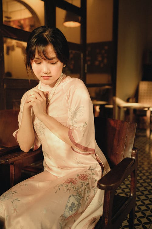Young contemplative ethnic female in ornamental apparel sitting with clasped hands on armchair at home while looking down