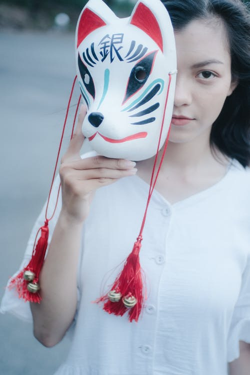 Crop attentive Asian woman with carnival mask on city street