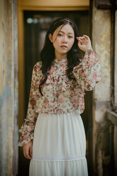 Stylish Asian woman in old house with shabby walls