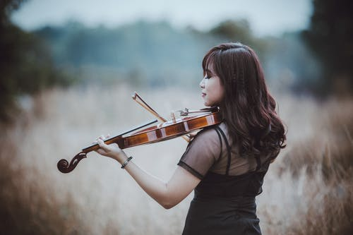 Stylish Asian violinist playing violin in field in countryside