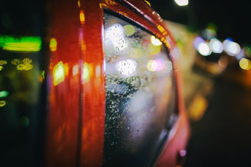 Vehicle with wet glass on night street with glowing lights