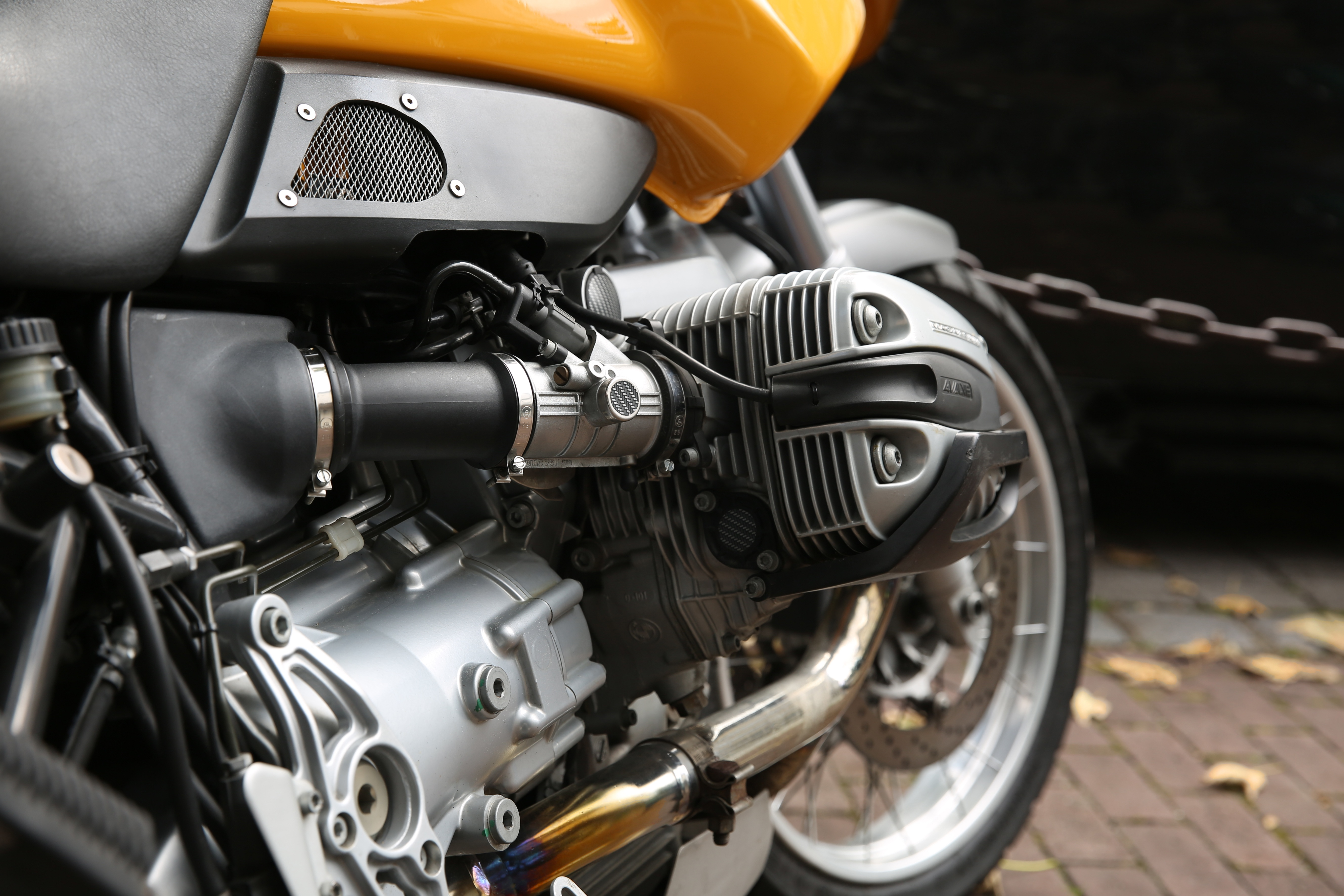 Yellow and Gray Motorcycle Parks Near Chain Rail