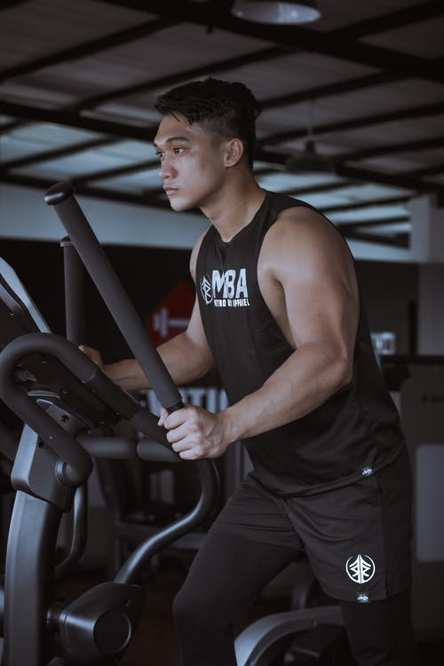 Side view of determined male in sportswear with biceps exercising on ellipsoid machine in gym during cardio workout in daytime