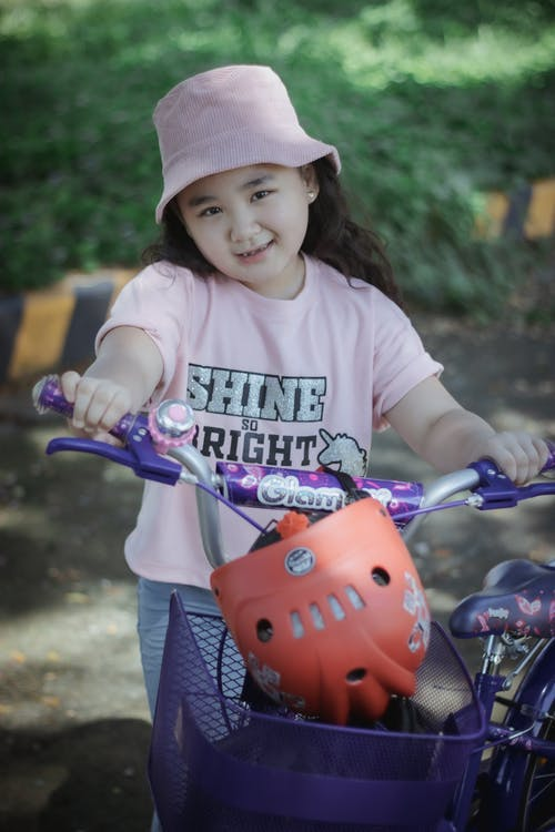 Happy little Asian girl standing near bicycle on street