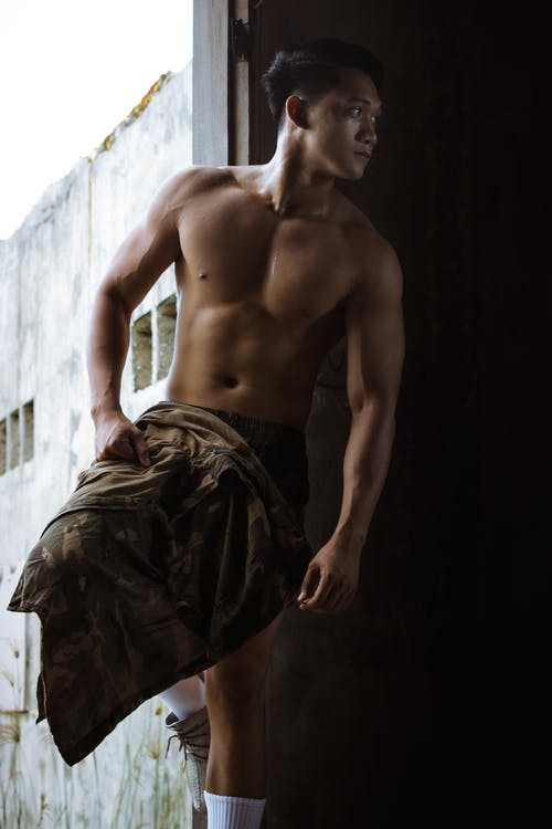 Muscular male with naked torso looking away while standing in doorway of shabby building with cape in hand in daylight