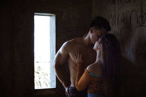Anonymous couple kissing in shabby house