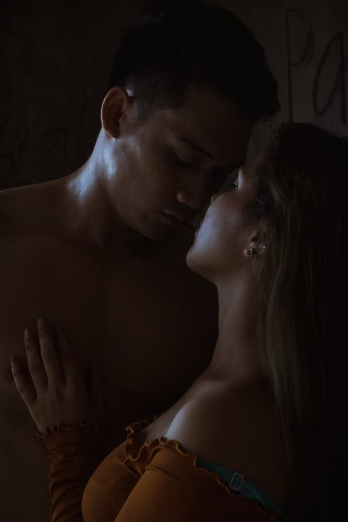 Anonymous couple embracing in dark room