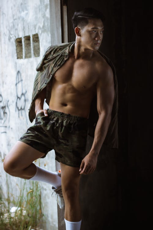 Serious male with naked torso wearing shorts leaning on shabby wall with obscene drawing while standing with hand in pocket and shirt on shoulder and looking away