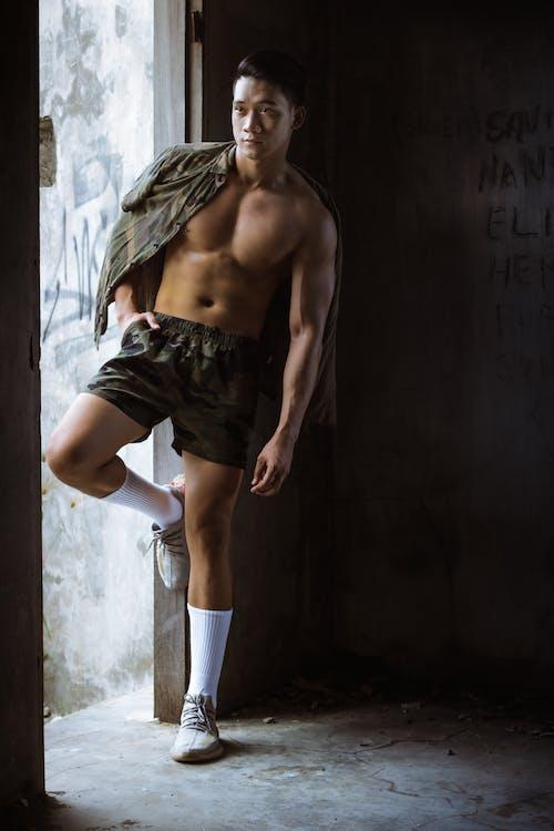 Strong shirtless man standing in doorway