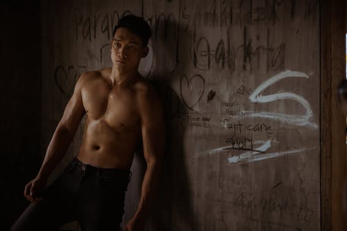 Masculine male with naked torso looking away while standing in abandoned building near shabby wall with graffiti in daylight inside