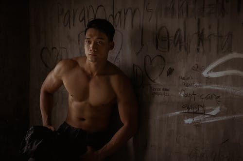 Muscular man leaning on wall