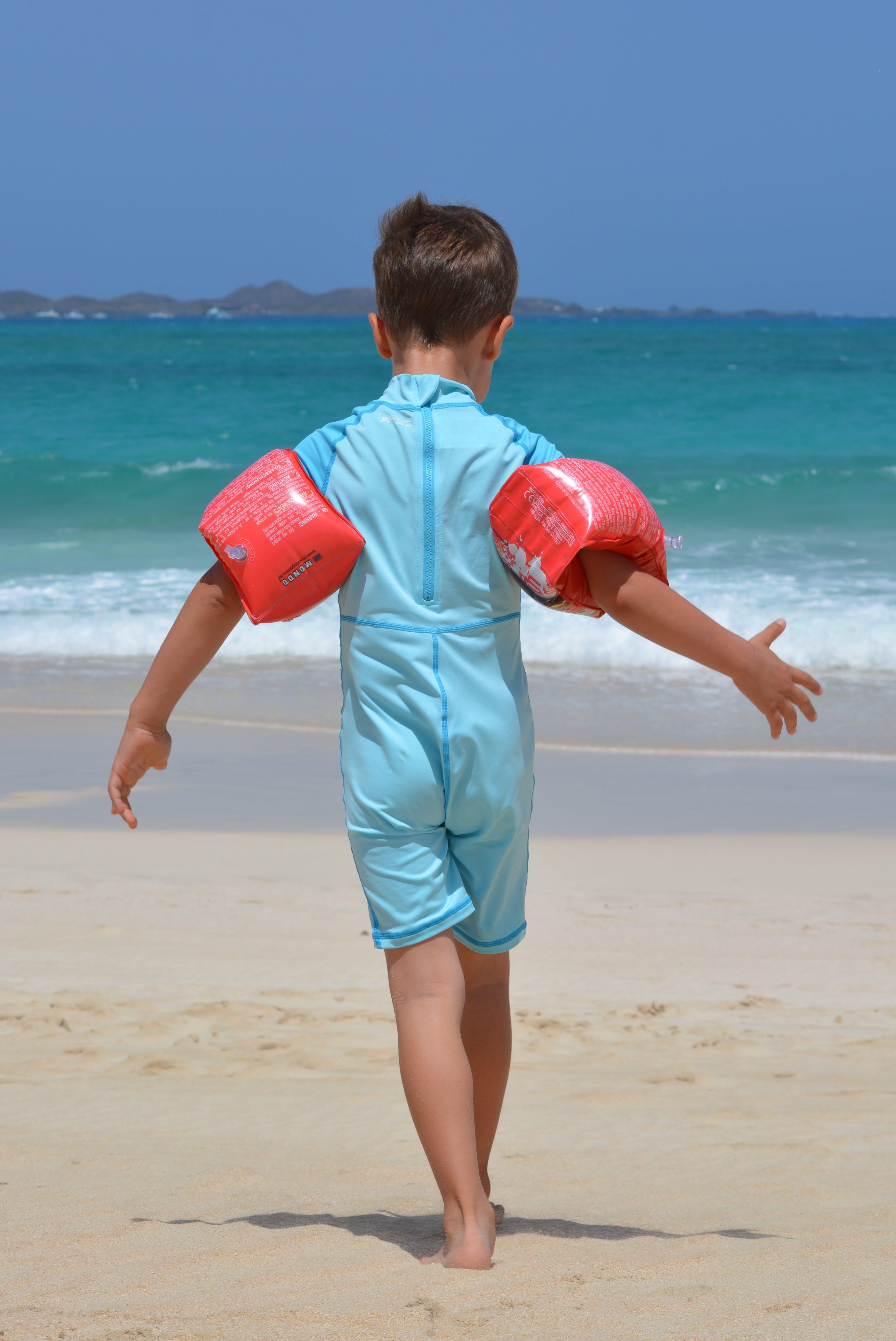Boy on Blue Onesie on Beach during Day