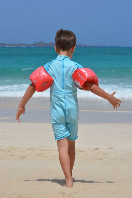 Boy on Blue Onesie on Beach during Day